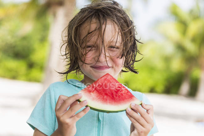 Sorrindo menino comendo melancia fatia ao ar livre na praia . — Fotografia de Stock