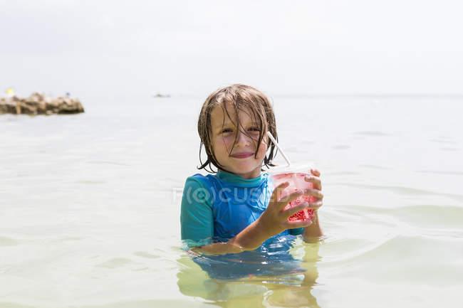 Sorridente bambino in camicia bagnata in acqua oceanica contenente bevanda alla frutta . — Foto stock