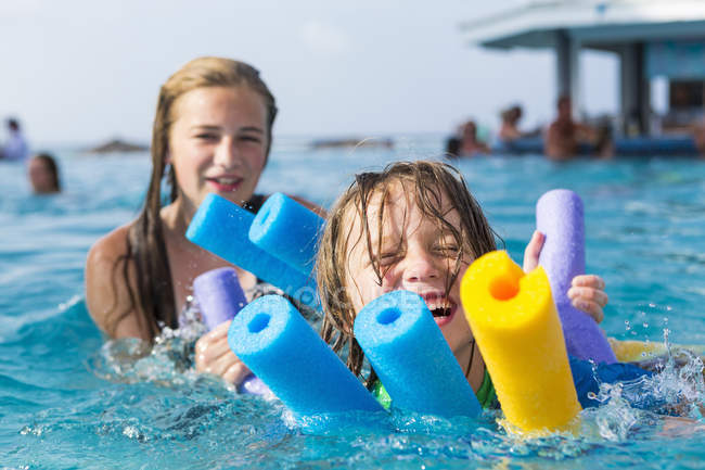 Siblings playing in pool in colorful floats. — Stock Photo