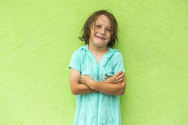 Smiling preschooler boy posing with arms crossed in front of green wall. — Stock Photo