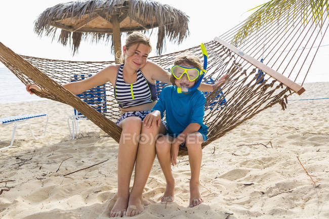 Teenage girl and brother sitting on hammock on sandy beach. — Stockfoto