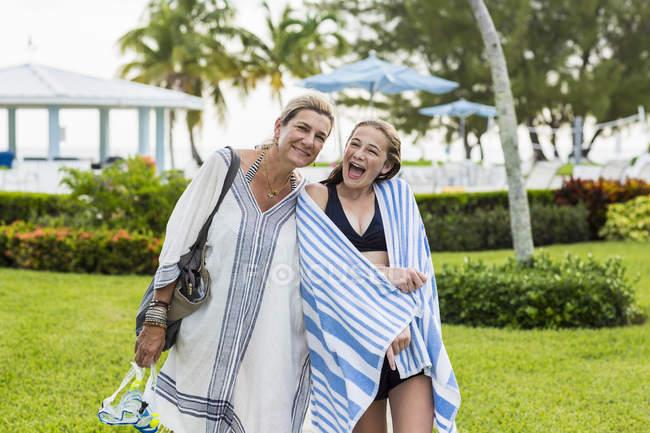 Mutter mit Tochter, die in der Kamera auf Urlaub Resort. — Stockfoto