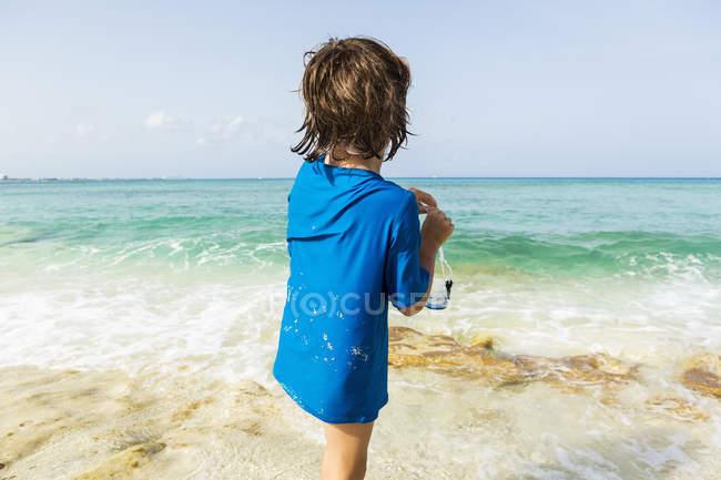 Дошкольник готовится надеть маску для сноркелинга на пляже. — стоковое фото