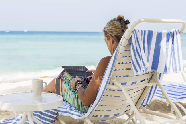 Adulto feminino executivo usando smartphone na praia, Grand Cayman Island — Fotografia de Stock