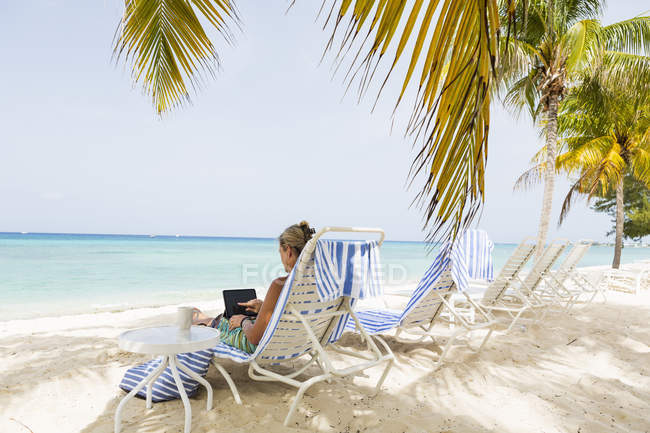 Executivo feminino adulto usando laptop na praia, Grand Cayman Island — Fotografia de Stock