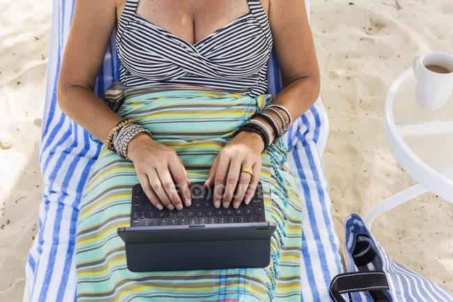 Mujer adulta que usa computadora portátil en la playa, Isla Gran Caimán - foto de stock