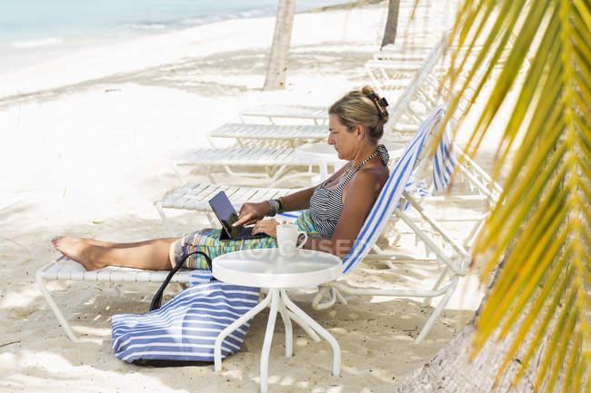 Adult woman using laptop on beach, Grand Cayman Island — Stock Photo