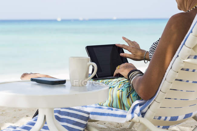 Adulto feminino executivo usando laptop na praia, Grand Cayman Island — Fotografia de Stock