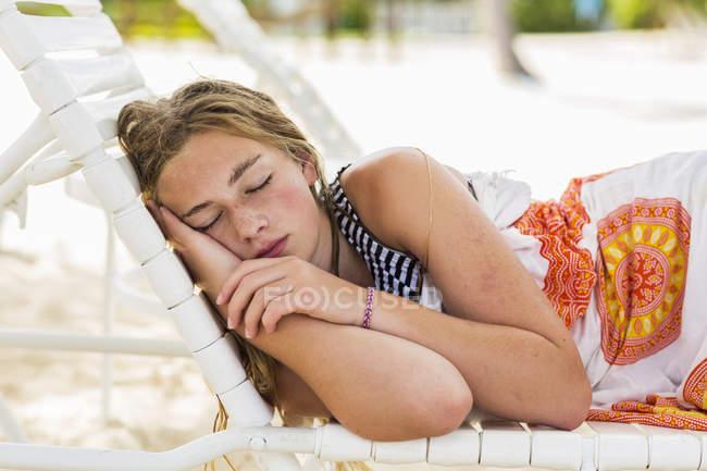 Teenage girl sleeping in beach chair. — Stock Photo