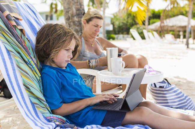 Menino pré-escolar usando laptop com mãe na praia . — Fotografia de Stock