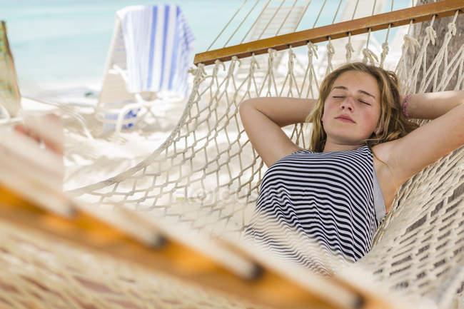 Teenage girl relaxing in hammock on tropical beach. — Stock Photo