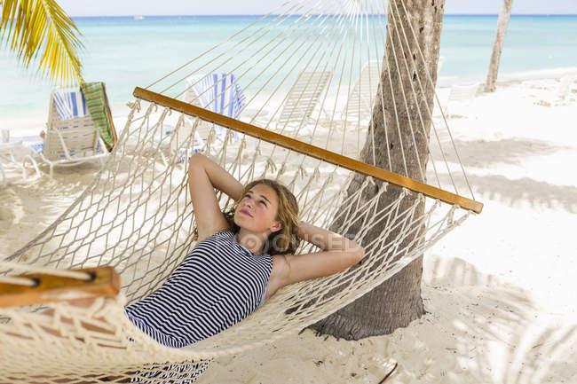 Девочка-подросток отдыхает в гамаке на тропическом пляже. — стоковое фото
