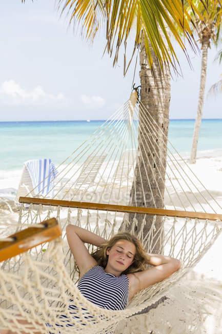 Девочка-подросток отдыхает в гамаке на тропическом пляже . — стоковое фото