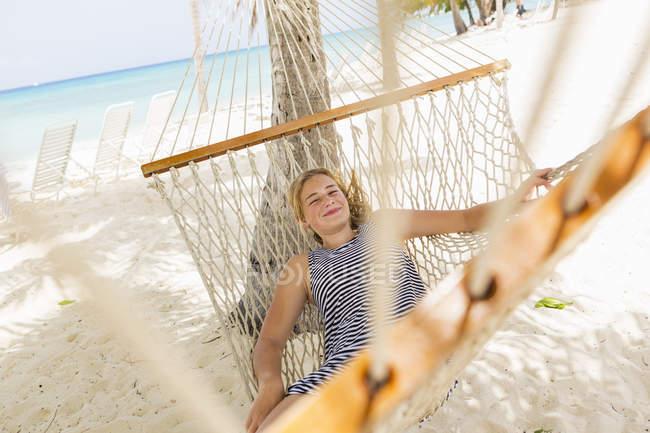 Ragazza adolescente rilassante in amaca sulla spiaggia tropicale. — Foto stock