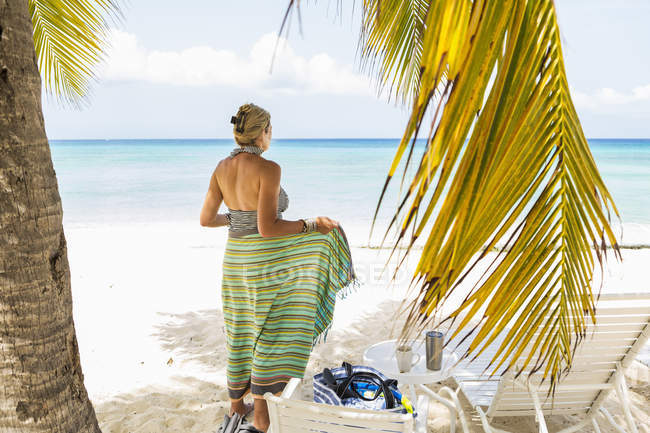 Взрослая женщина, завернутая в цветной саронг на пляже — стоковое фото