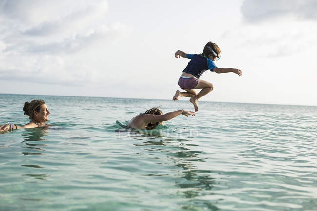 Adult woman watching as children playing in ocean water — Stock Photo