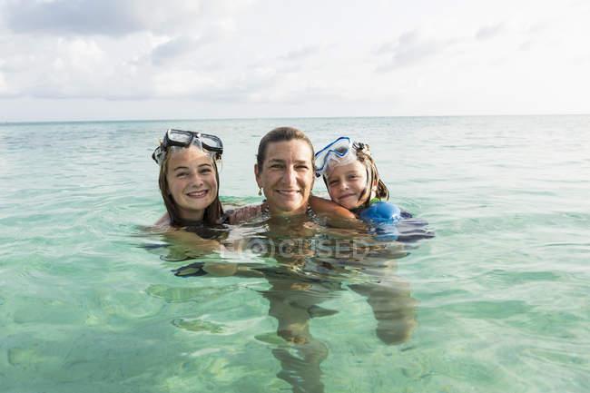Взрослая женщина, стоящая в океанской воде на закате с детьми — стоковое фото