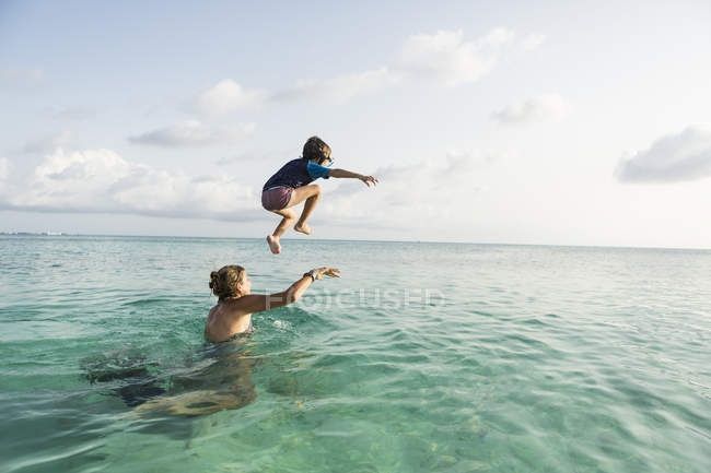 Preschooler son from mother shoulders leaping into ocean at sunset. — Stock Photo