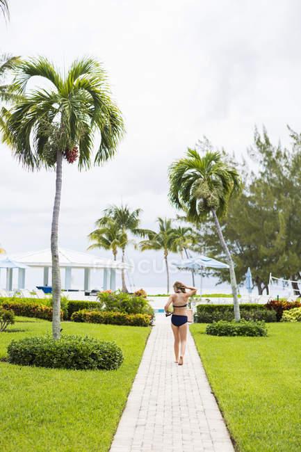 Заднього виду дівчинки підлітка ходити до басейну на курорті. — стокове фото