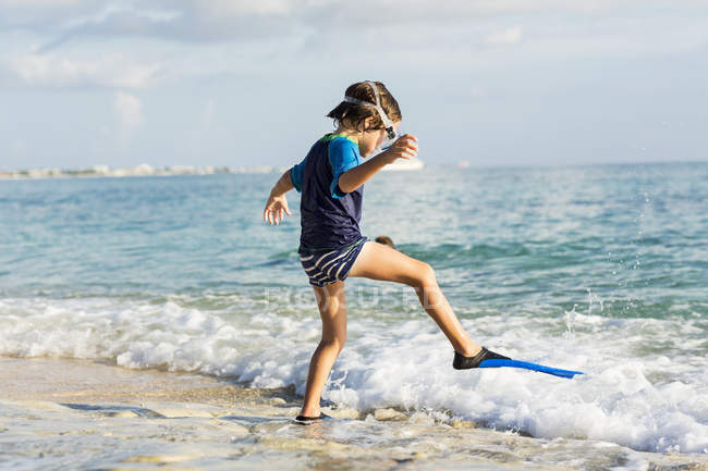 Little boy in swim fins trying water on sandy beach. — Stock Photo
