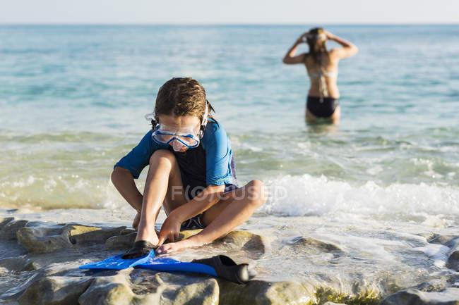 Little boy putting swim fins on sandy beach. — Stock Photo