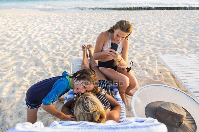 Мать с детьми наслаждаются пляжем на закате, остров Гранд-Кейман — стоковое фото
