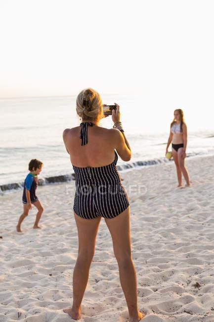 Мать фотографирует детей, наслаждающихся пляжем на закате, остров Гранд-Кейман — стоковое фото