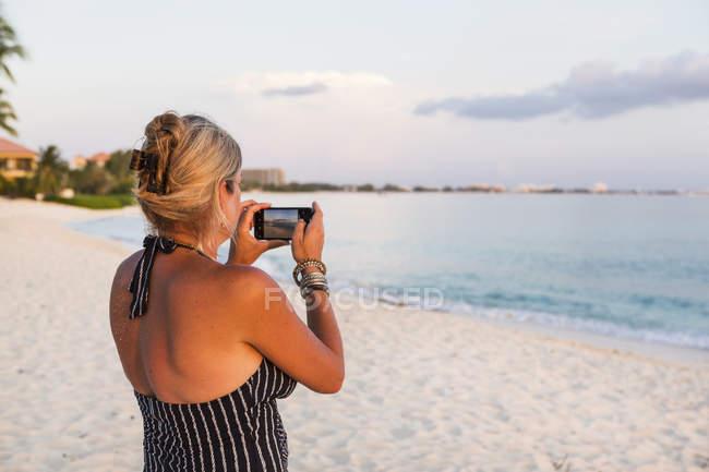 Mulher adulta tirando foto com smartphone na praia — Fotografia de Stock