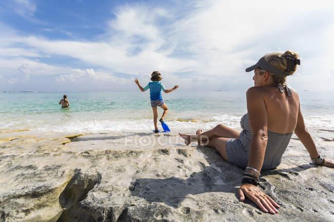 Маленький хлопчик, що ходить по воді, коли мама дивиться на острів Ґранд Кайман.. — стокове фото