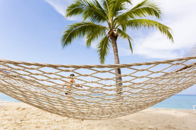 Hammock, green palm tree and people in background, Grand Cayman Island — Stock Photo