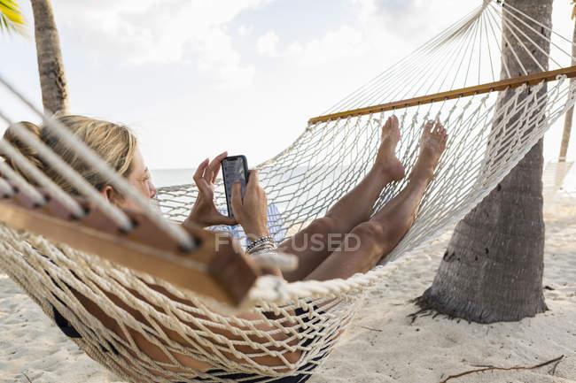 Relaxante mulher madura em rede usando smartphone . — Fotografia de Stock