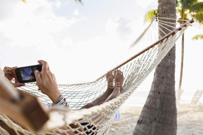 Relaxante mulher na rede usando smartphone . — Fotografia de Stock