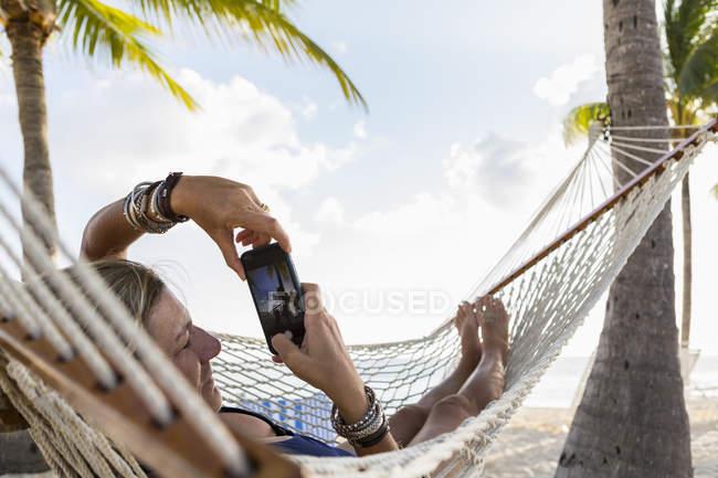 Relaxing mature woman in hammock using smartphone. — Stock Photo