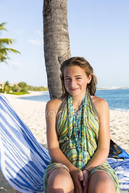 Улыбающаяся девушка-подросток, сидящая в пляжном кресле, Большой Кайман-Айленд. — стоковое фото