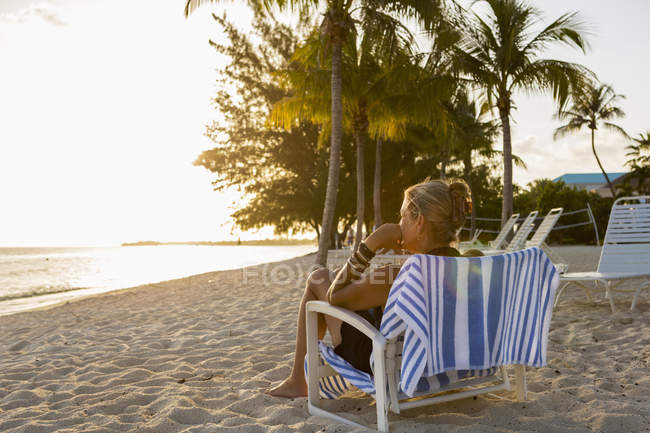 Adult woman sitting in beach chair, Grand Cayman Island — Stock Photo