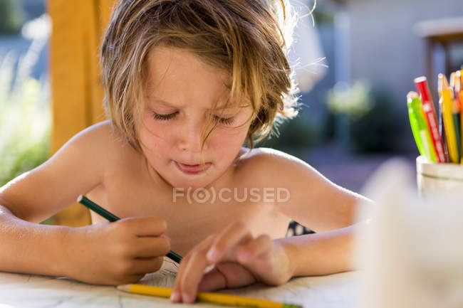 Shirtless little boy drawing with colored pencils outdoors. — Stock Photo