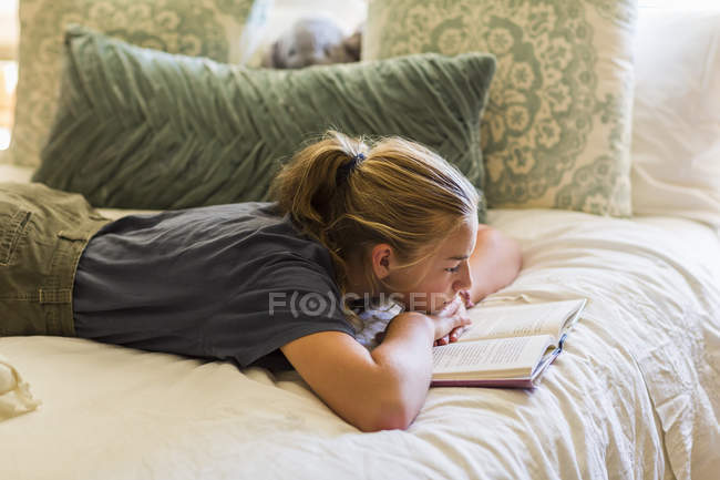 Teenage girl lying in bed and reading by window light. — Stock Photo