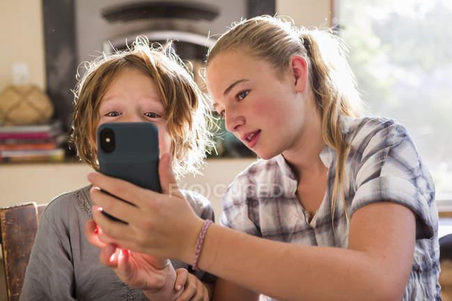 Девочка-подросток и младший брат, держащий смартфон и делающий селфи . — стоковое фото