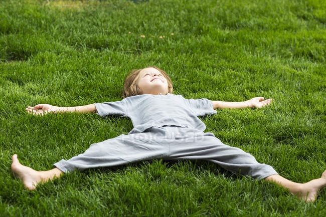 Elementary age boy lying down on lush green lawn looking up — Stock Photo
