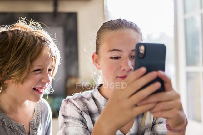 Брат и сестра держат смартфон и смотрят на экран . — стоковое фото