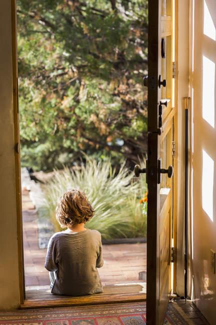 Vue arrière du petit garçon assis sur le seuil de la porte tôt le matin — Photo de stock