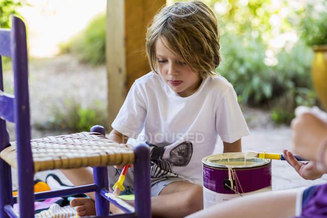Мальчик младшего возраста рисует кресло на крыльце с сестрой — стоковое фото