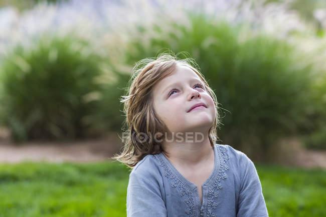 Старшеклассник отдыхает на пышной зеленой лужайке и смотрит вверх — стоковое фото
