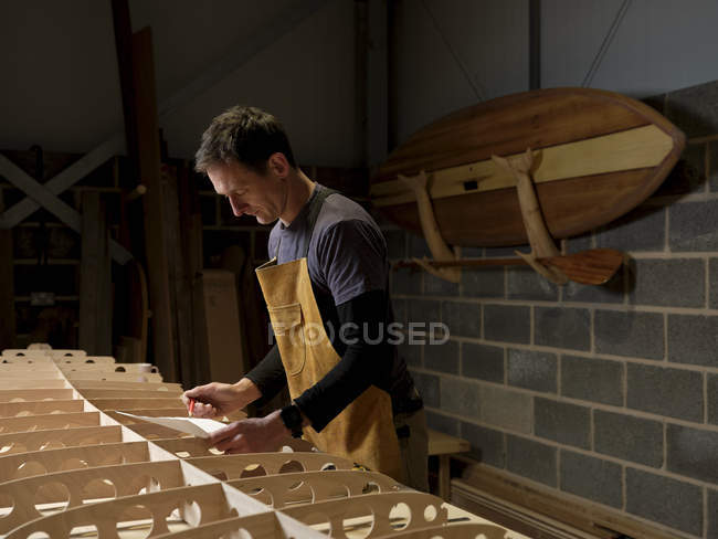 Man at work standing over wooden paddleboard in workshop holding paper and pencil — Stock Photo