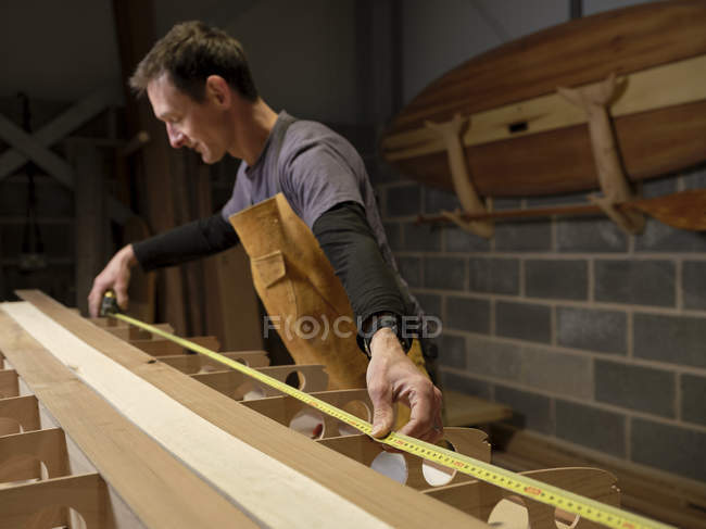 Man in workshop using expanding tape measure to making wooden paddleboard — Stock Photo