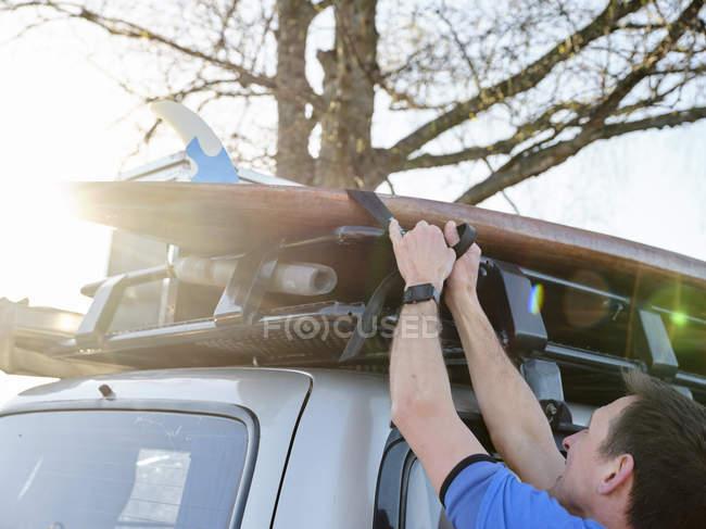 Мужчина прикрепляет поддон к крыше автомобиля на открытом воздухе при солнечном свете — стоковое фото