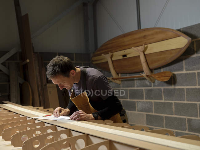 Mann mit kleinem Metalllineal beim Holzpaddeln in Werkstatt — Stockfoto