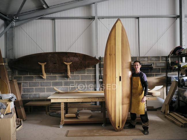 Portrait of man holding handmade wooden paddleboard in crafting workshop — Stock Photo