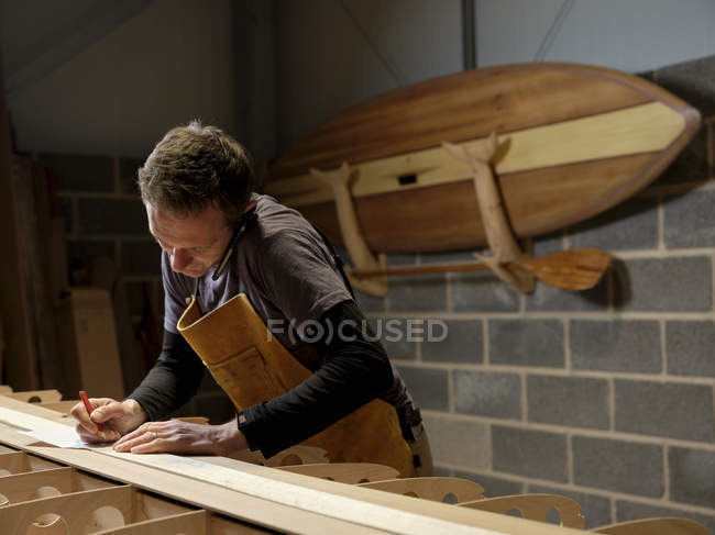 Paddleboard-Hersteller nutzt Handy in Werkstatt — Stockfoto