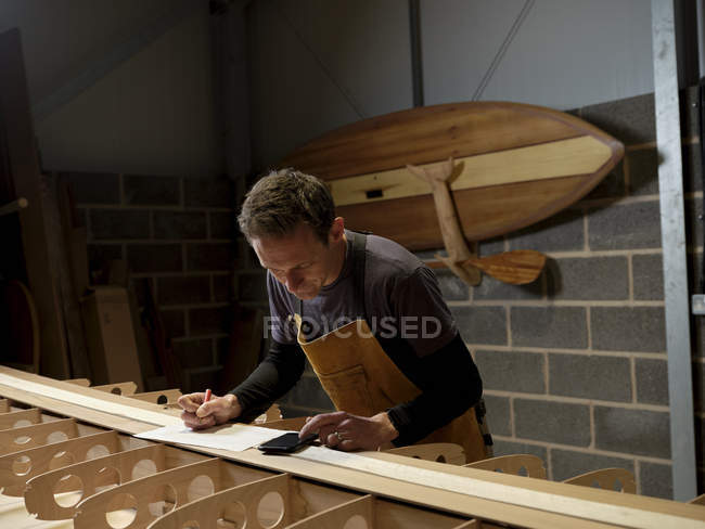 Paddleboard maker using digital device in crafting workshop — Stock Photo